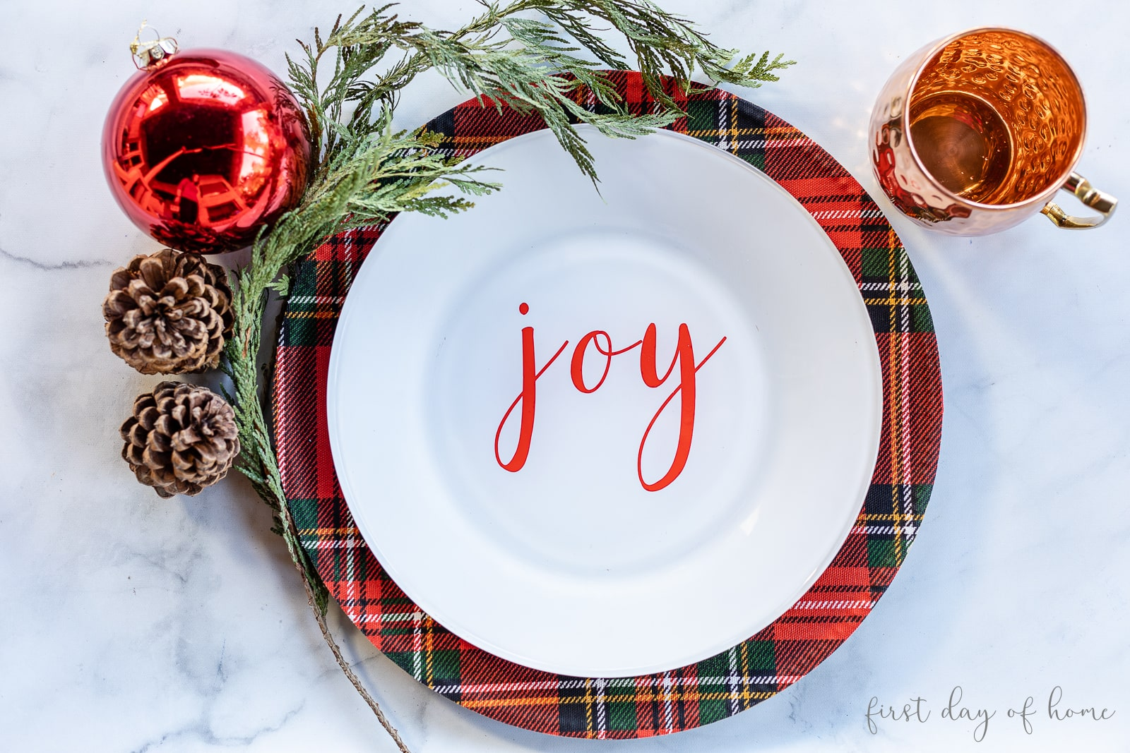 "Tartan plaid charger plate with white plate reading ""Joy"" next to copper mug and Christmas decor"