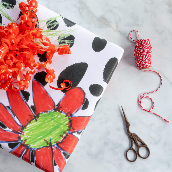 Present wrapped in colorful DIY wrapping paper in floral and black spotted pattern with scissors and baker's twine