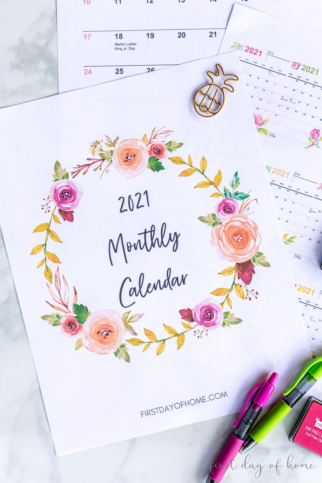 Printable 2021 calendar pages shown with pineapple paper clips, colorful pens and ink pad