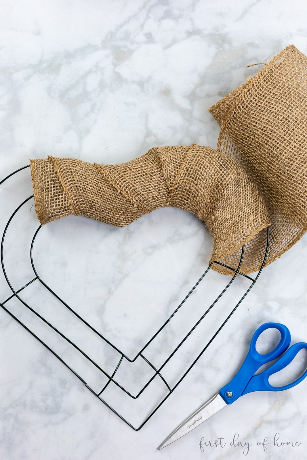 Heart shaped wreath wrapped in neutral burlap ribbon