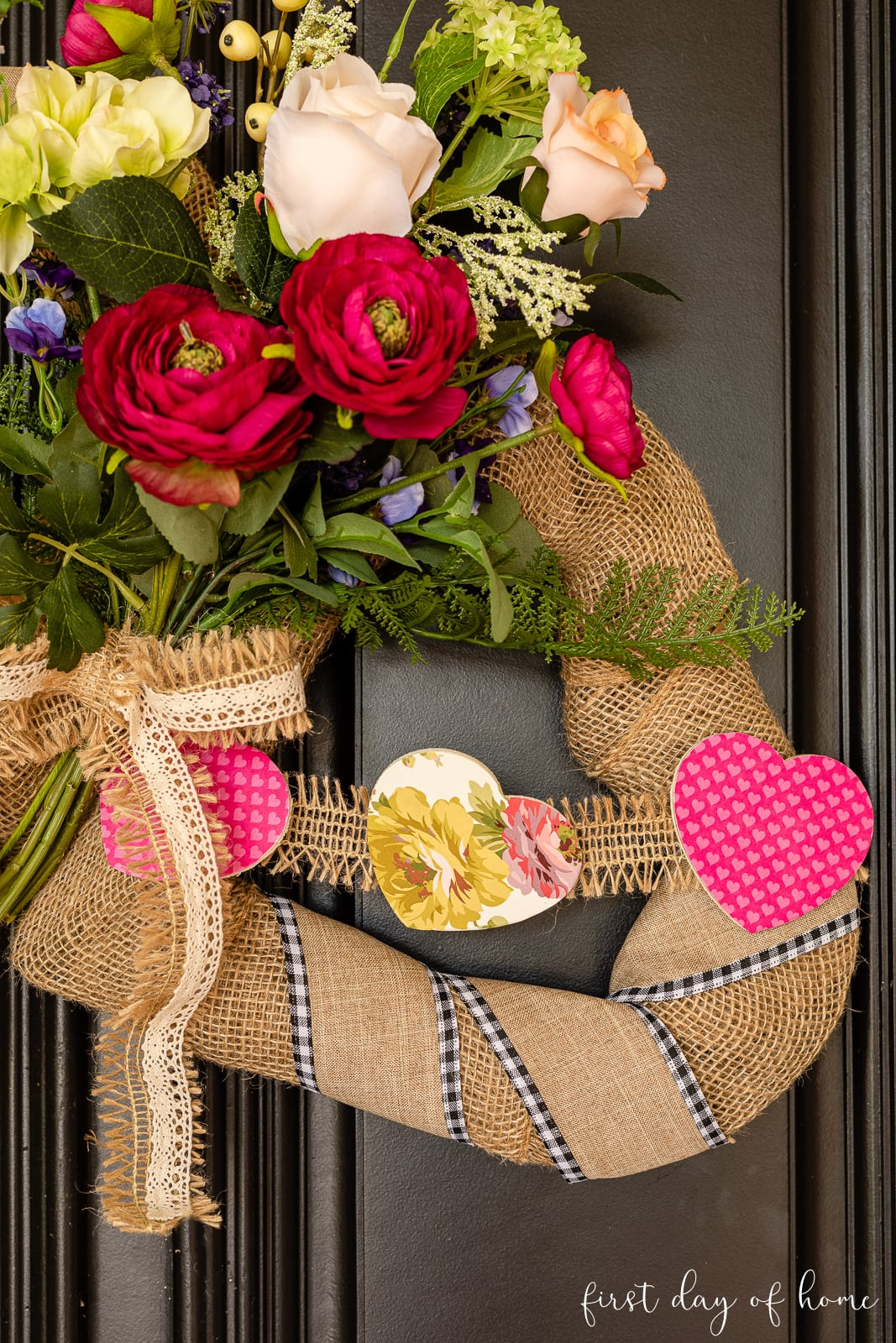 Close up of burlap Valentine wreath with wooden heart garland and faux florals