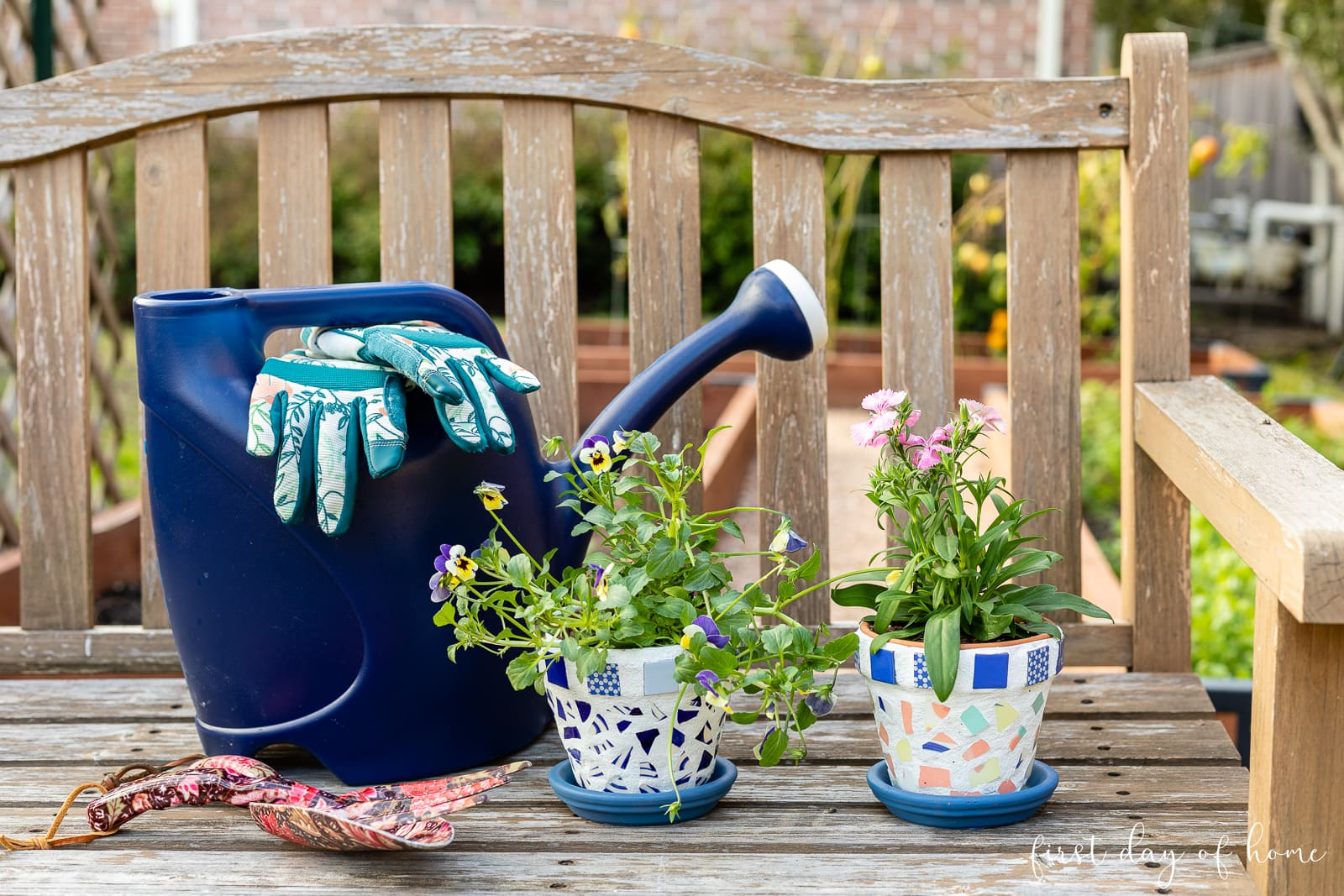 Finished mosaic flower pots with gardening tools and watering can on bench