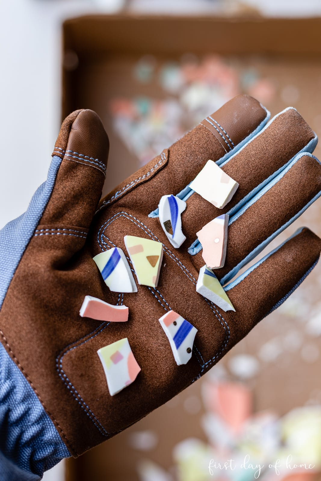 Mosaic tile pieces from broken plate in a gloved hand