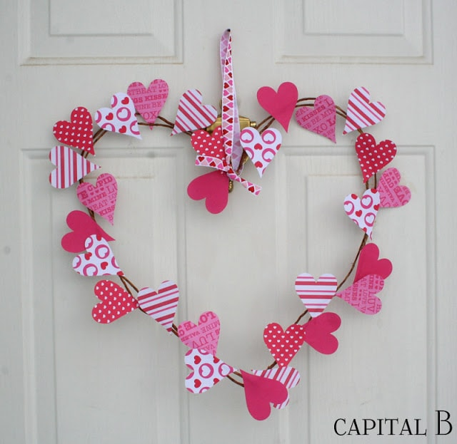 Heart shaped wreath with paper heart cutouts on white front door