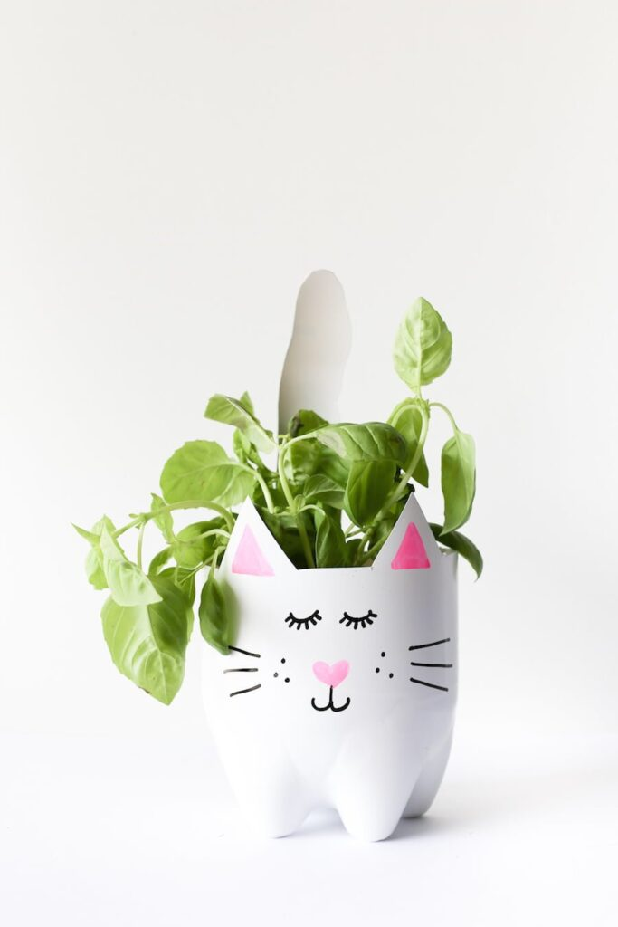 Painted flower pot with a cat design made from soda bottles