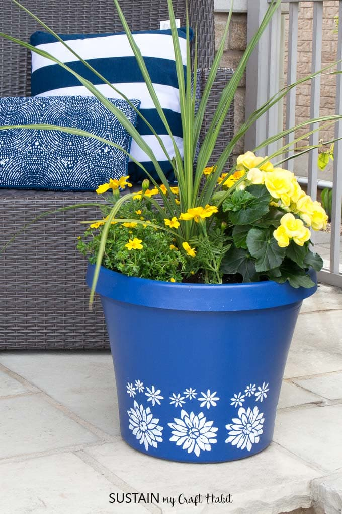 Blue flower planter with white stenciled flowers filled with yellow flowering plant