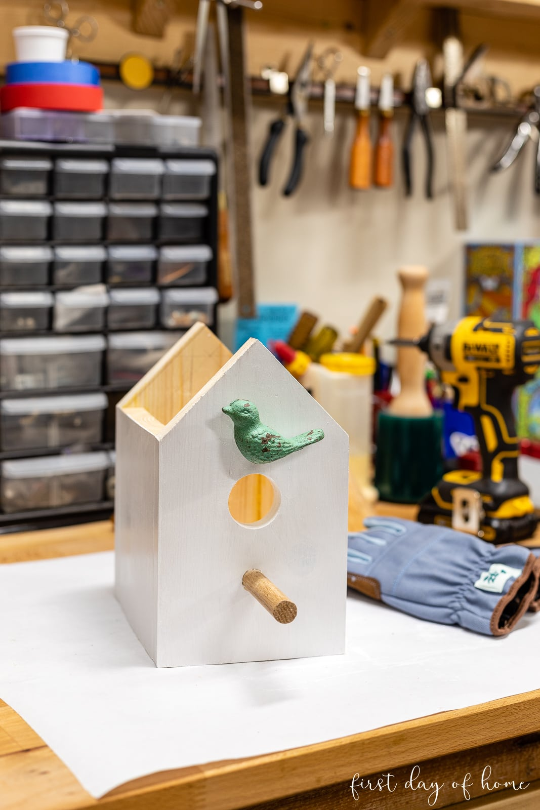 Painted DIY birdhouse on workbench