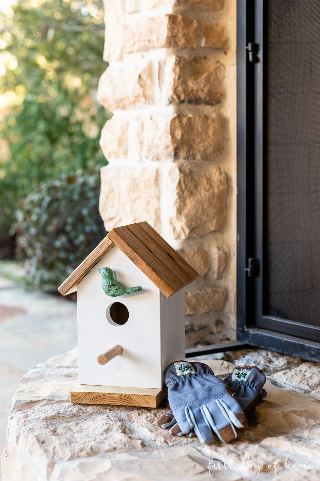 DIY birdhouse sitting on outdoor hearth with gardening gloves