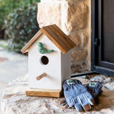Birdhouse on outdoor patio with gardening gloves