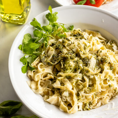 Pasta noodles with pesto sauce and arugula garnish