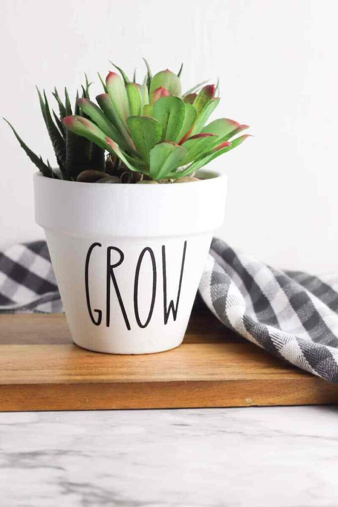 """Rae Dunn inspired flower pot with white paint and black letters reading """"Grow"""""""