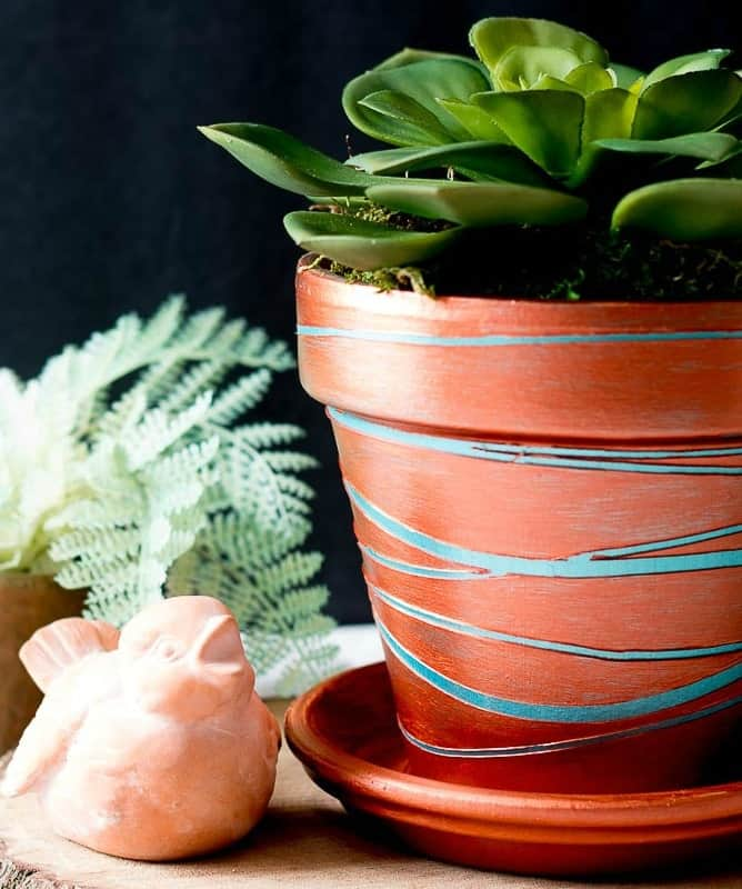 Copper clay pot with turquoise stripes filled with succulent plant