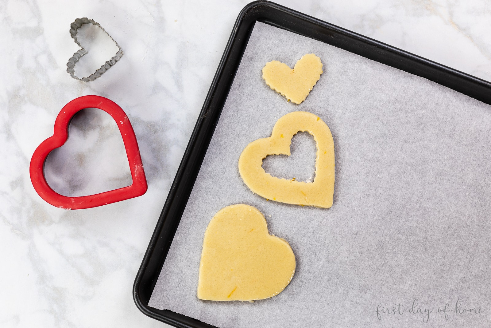 Heart shaped cookie shapes before baking with heart cookie cutters on counter