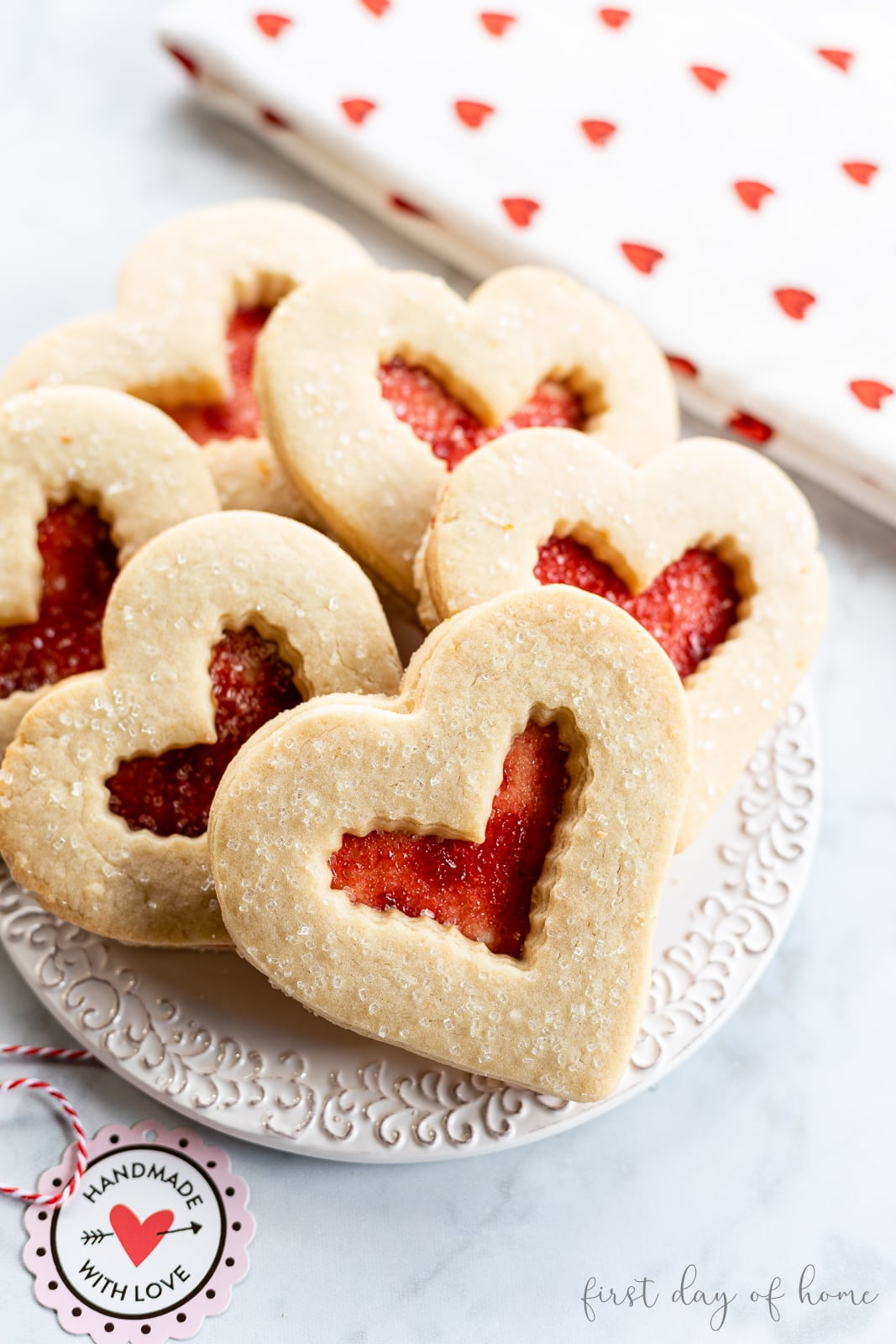 Heart shaped sugar cookies with jelly filling and tea towel with gift tag
