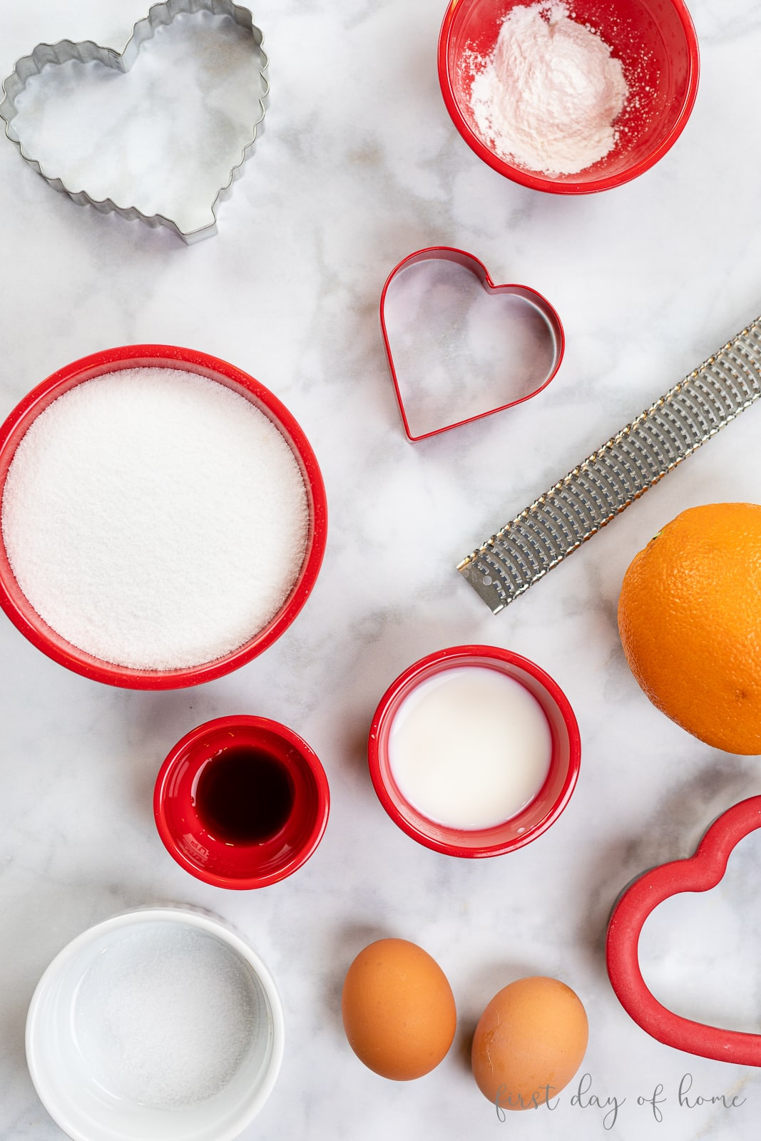 Ingredients for Valentine's Day sugar cookies recipe, including heart cookie cutters, sugar, vanilla and orange peel