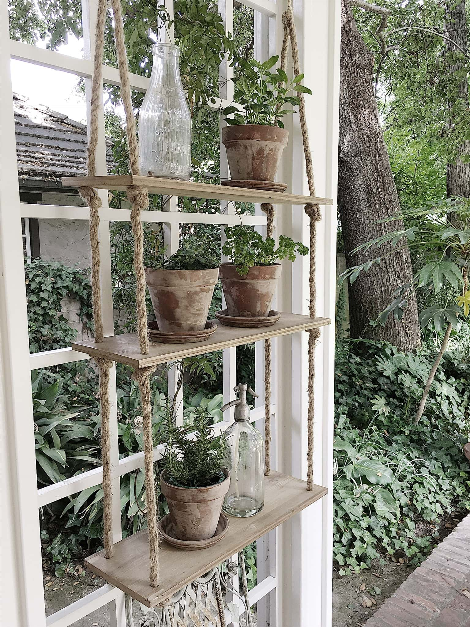 Aged terracotta pots sitting on outdoor hanging shelves