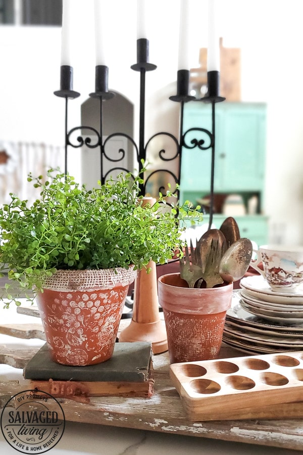 Shabby chic painted terracotta pots sitting on kitchen counter with books and kitchen accessories