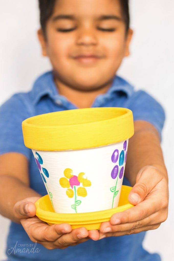 Fingerprint painted flower pot with child holding it