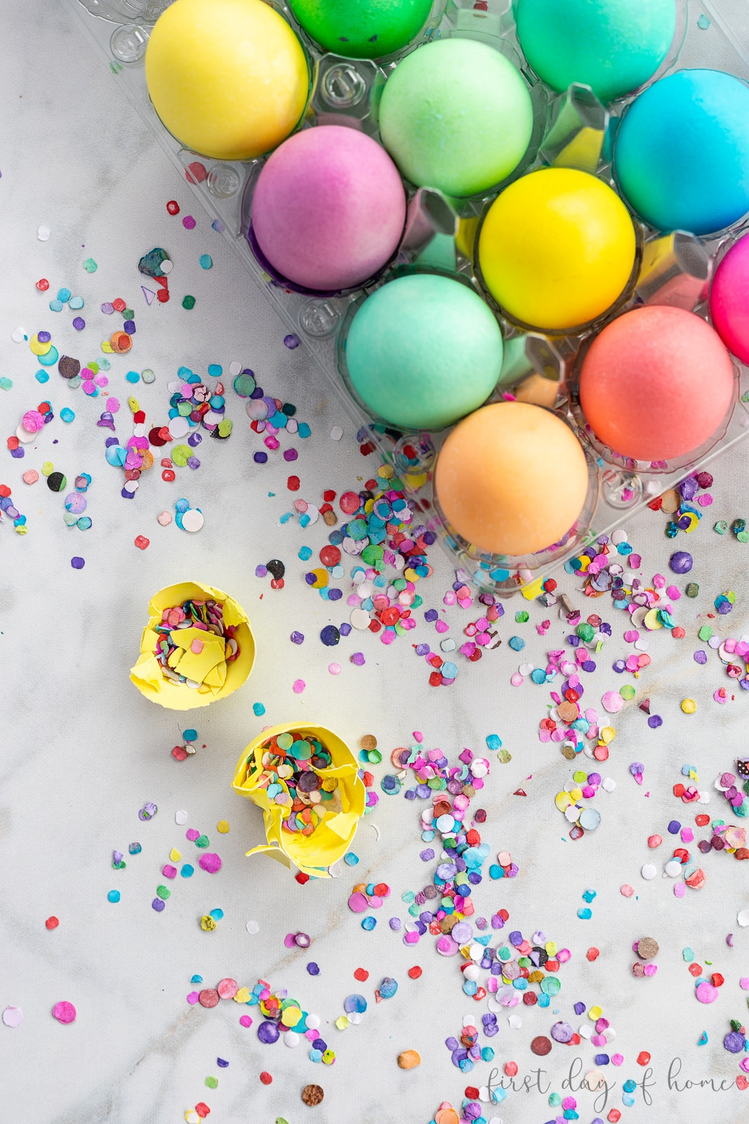 Colored Easter eggs with one egg cracked open to reveal confetti