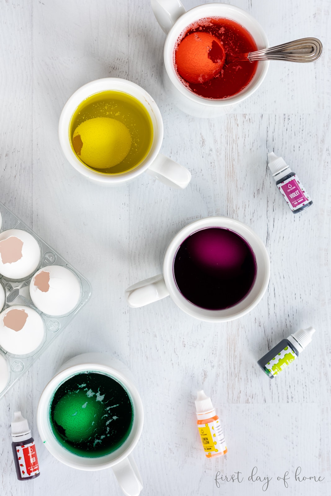 Dyeing eggs in mugs with food coloring mixture with food coloring bottles nearby