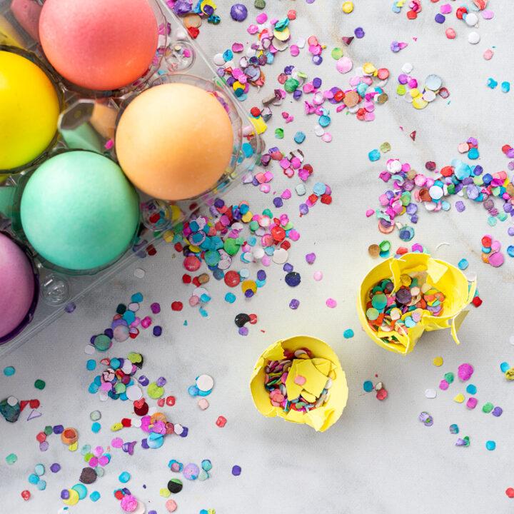 Colored eggs in carton with broken cascron (confetti filled egg) with confetti in background