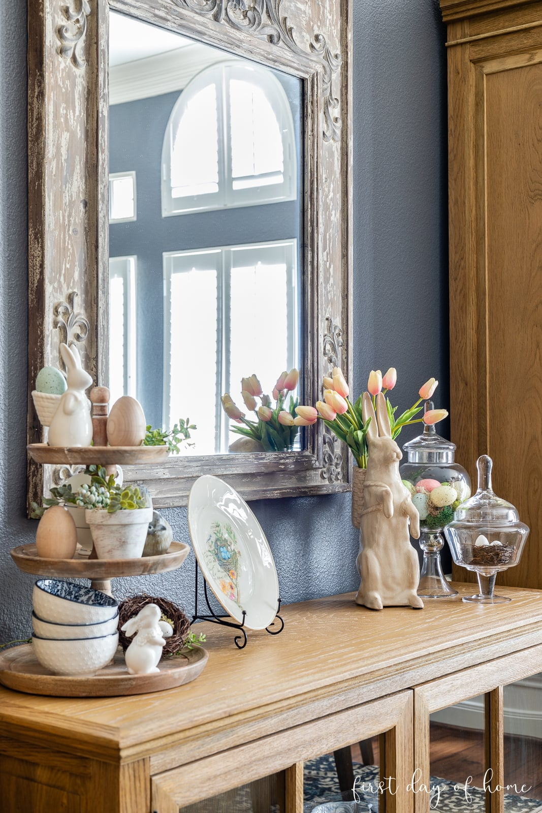 Spring home decor on sideboard, including bunny figurine, glass apothecary jars, tiered tray and decoupage plate