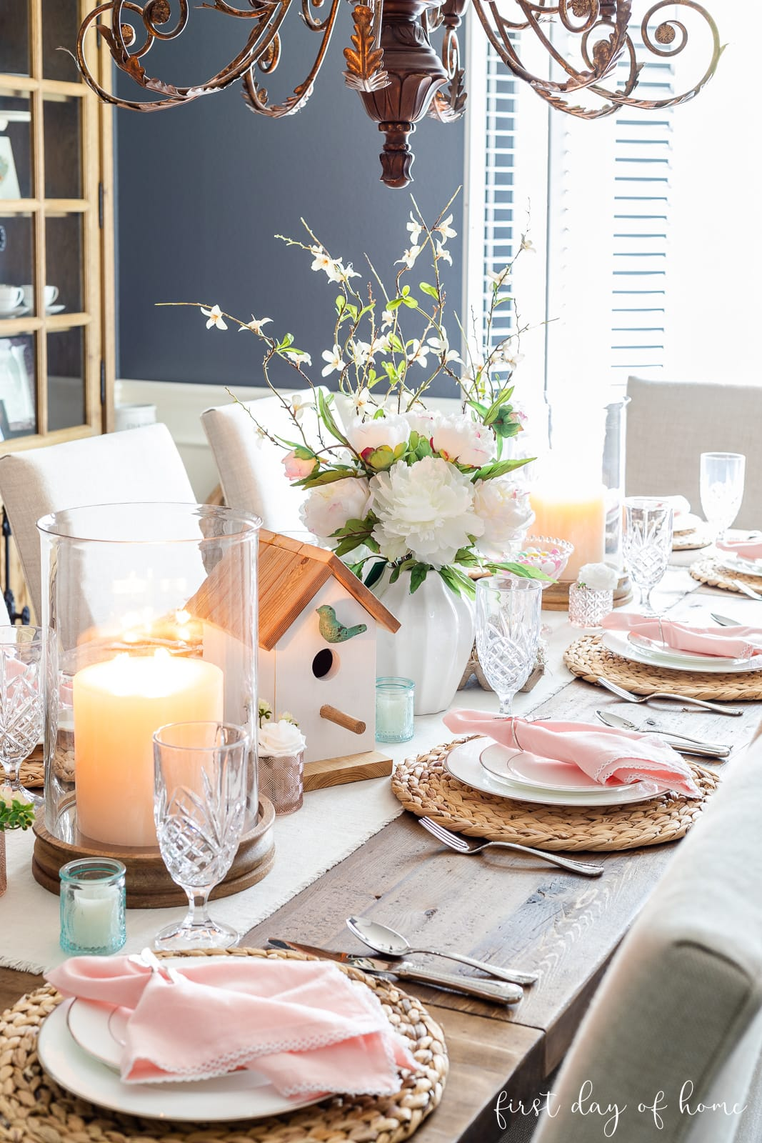 Spring table decor with birdhouse, pillar candles and pastel accents