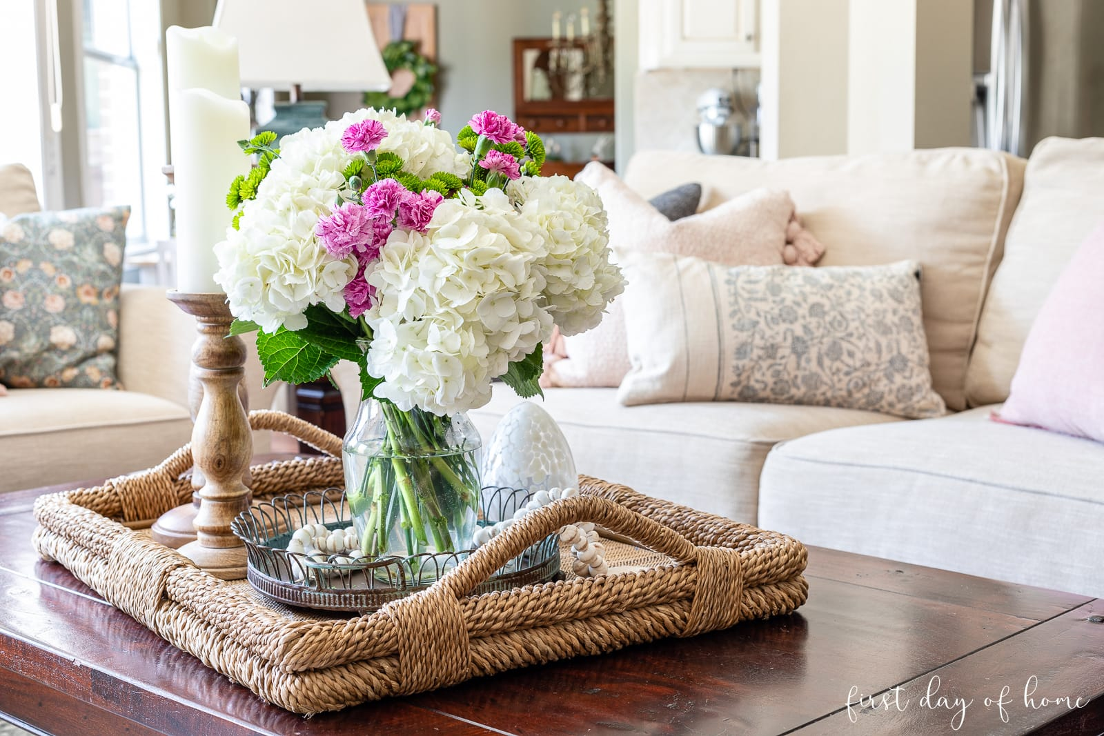 Coffee table centerpiece with real hydrangea floral arrangement, wooden bead garland, flameless candles and egg cloche