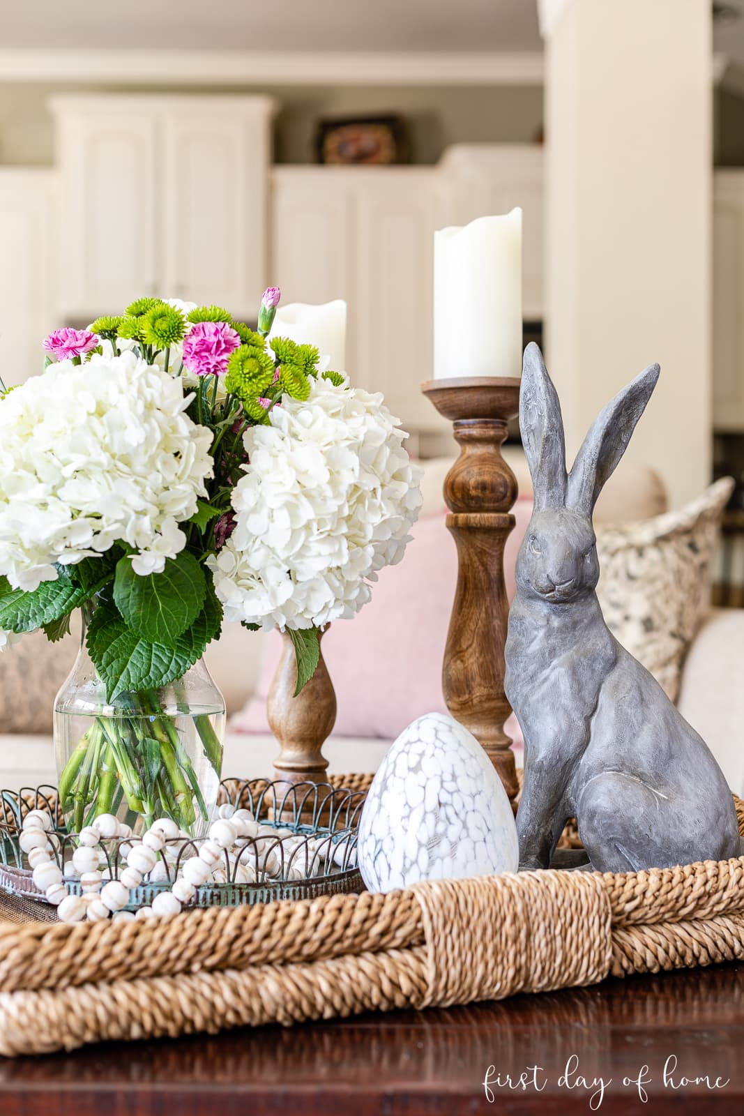 Spring coffee table decor with basket tray, bunny, candles, egg cloche and a fresh hydrangea floral centerpiece