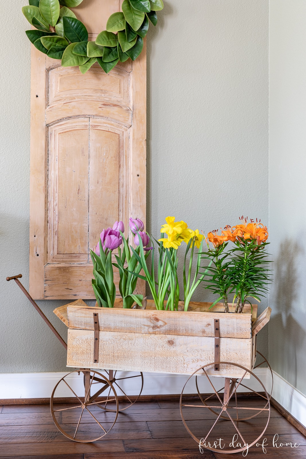 Four-wheeled decorative cart filled with tulips and lillies