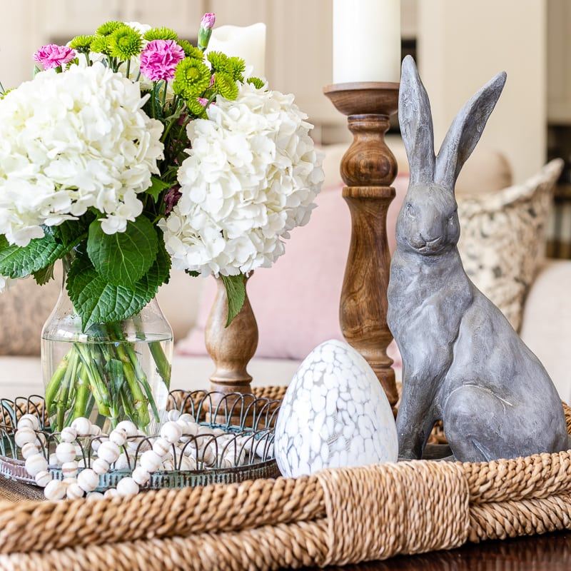 Spring centerpiece with basket tray containing candles, bunny figurine, egg cloche, candles and fresh hydrangea floral arrangement on coffee table