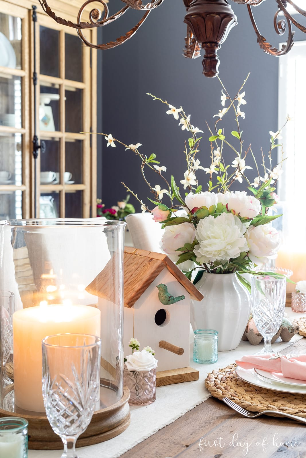 Spring table decor with pillar candles, birdhouse and floral centerpieces arrangement