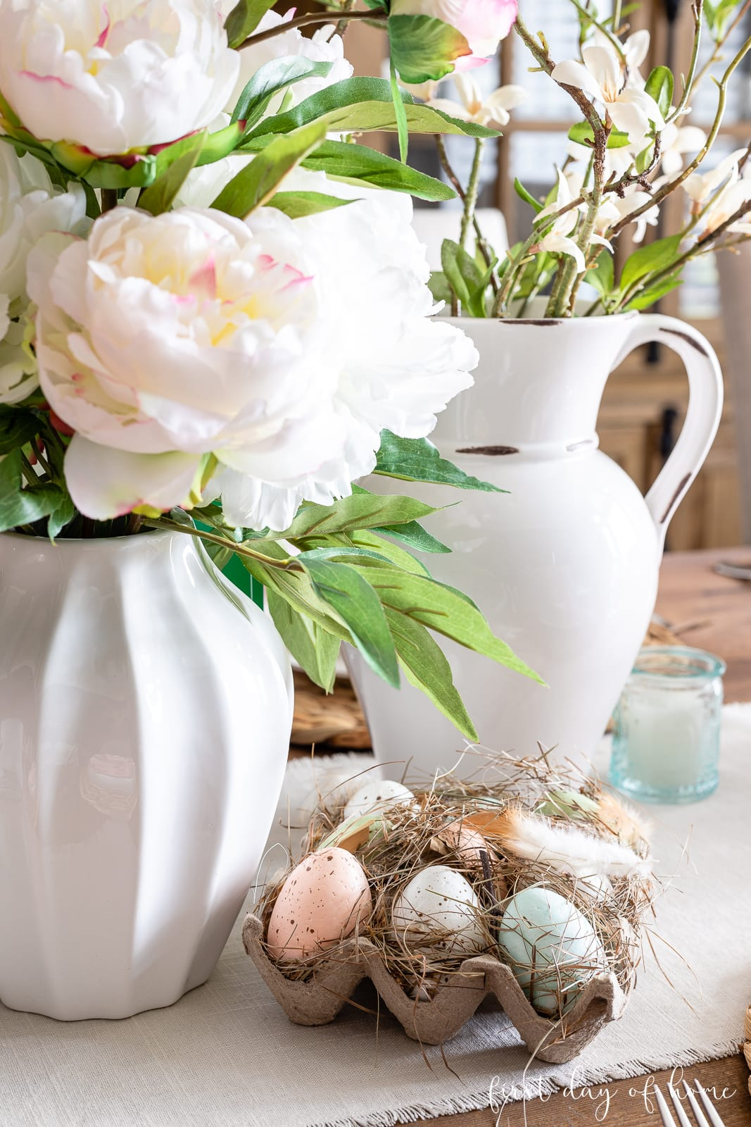 Spring table centerpiece with faux florals in vases and small half dozen eggs in a crate that resemble a nest