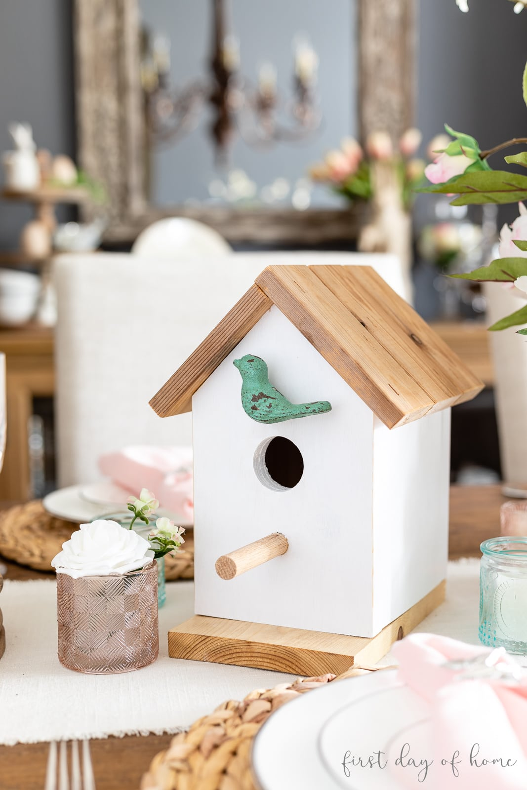 DIY birdhouse as spring table decor accent with small pink votives and floral arrangements