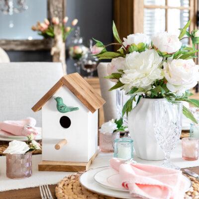 Birdhouse and floral arrangement centerpiece for spring table decor