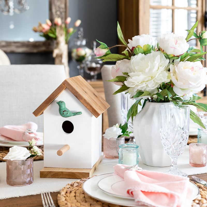 Birdhouse and floral arrangement centerpiece for spring table decor