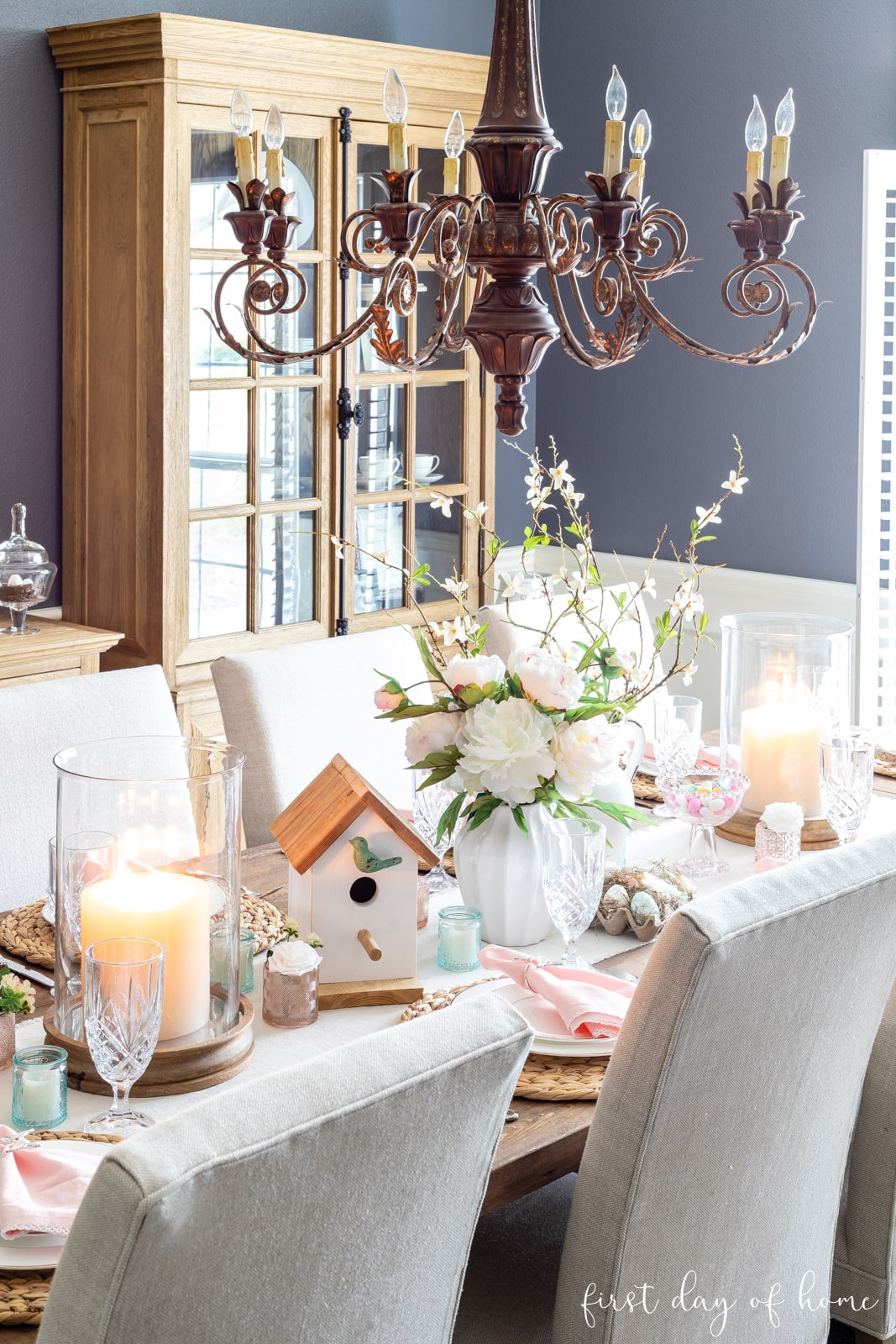 Spring tablescape with pastel blue and pink accents and birdhouse centerpiece with faux florals