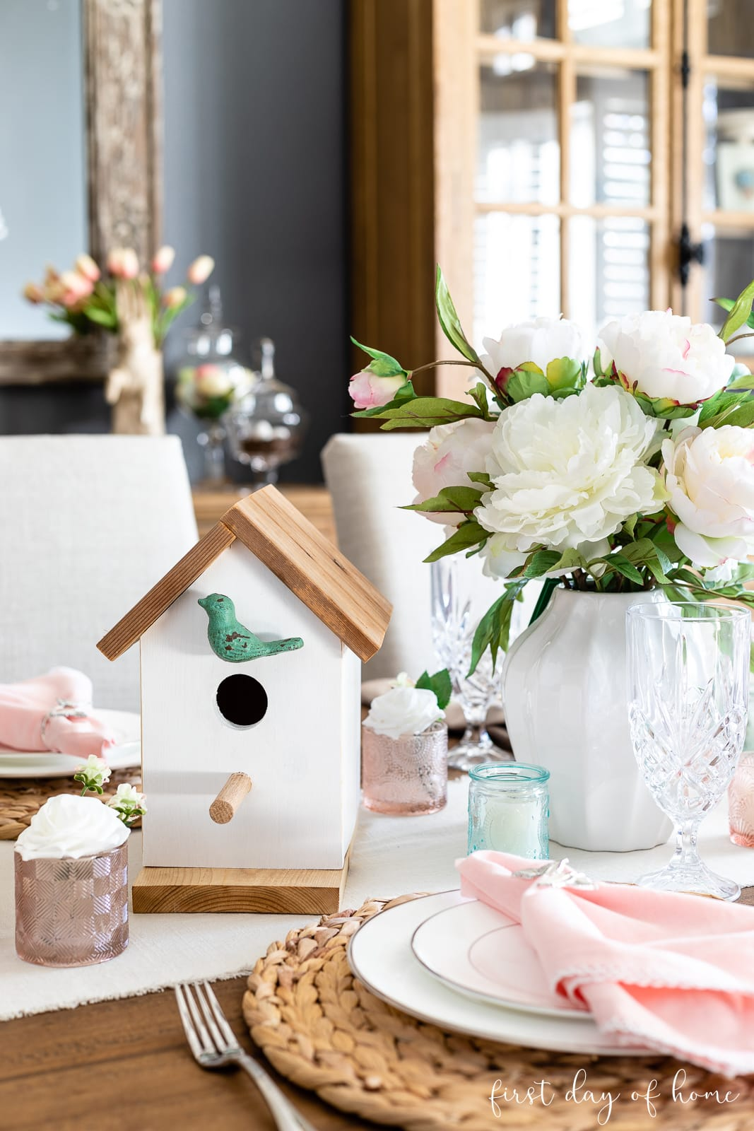 Spring table decor with birdhouse and floral arrangement as centerpiece with pastel pink and blue accents