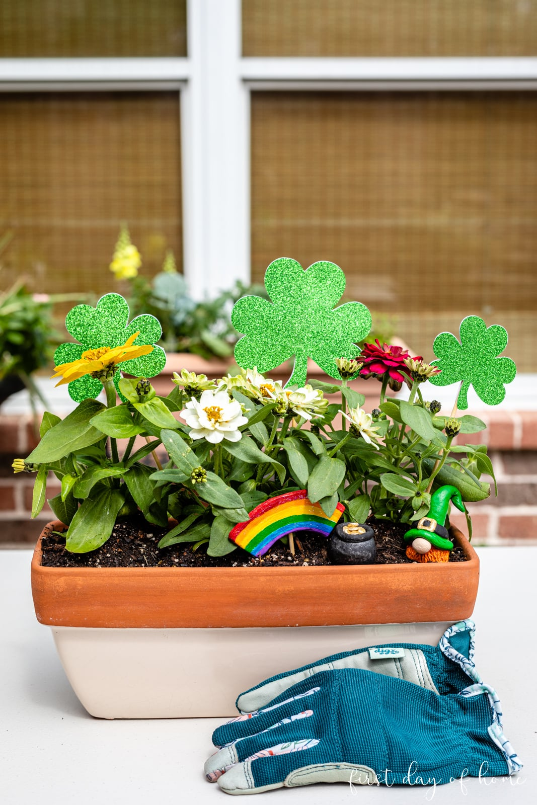 St. Patrick's Day themed fairy garden display with air dry clay gnome, pot of gold, rainbow and sparkling clover garden stakes