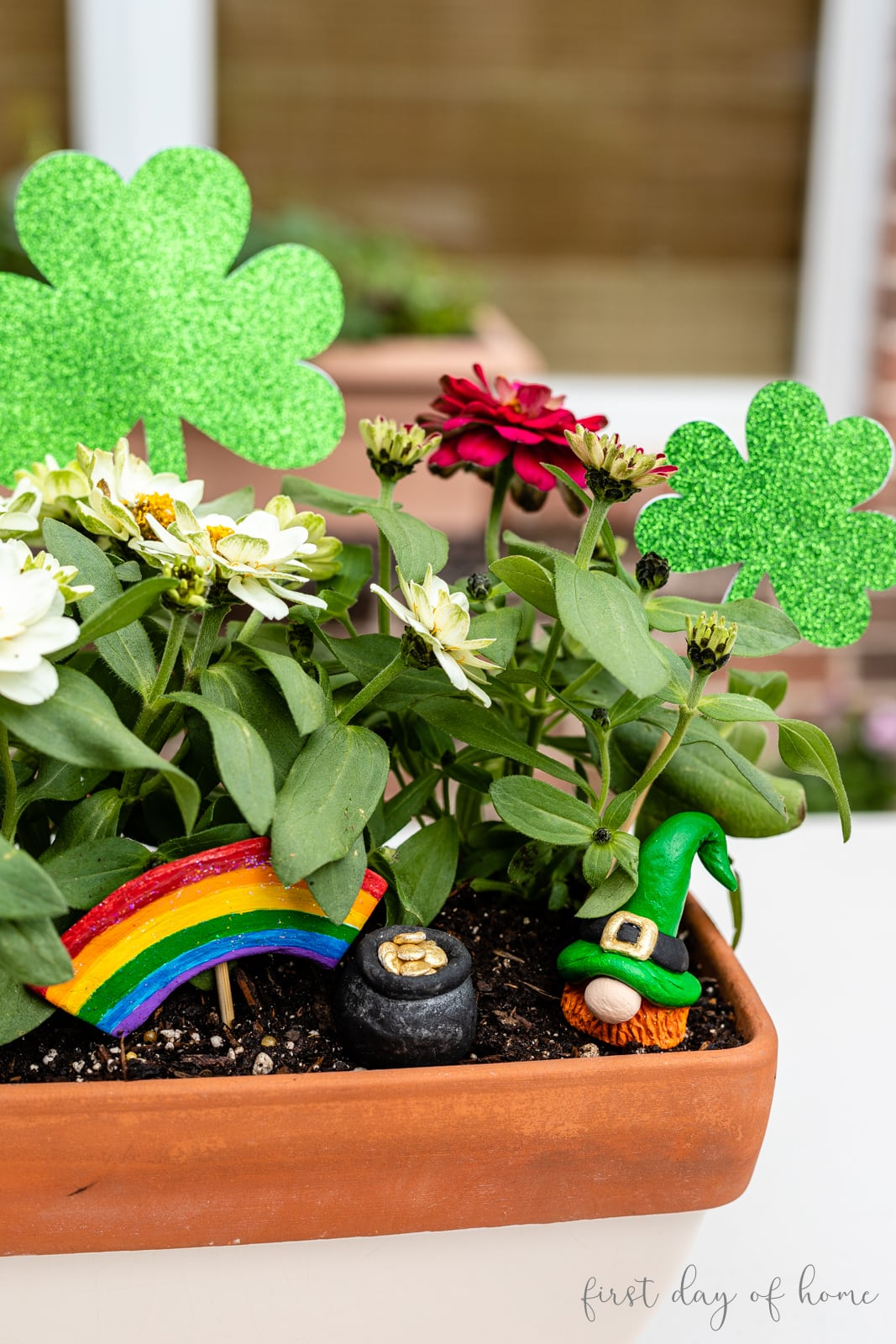 Leprechaun St. Patrick's Day gnome in a fairy garden with a rainbow and pot of gold all made from air dry clay