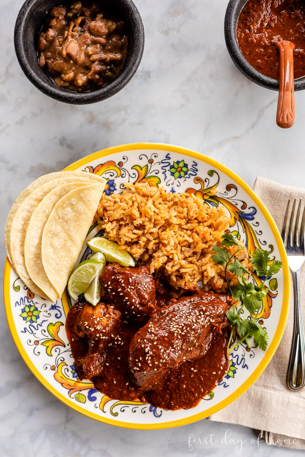 Chicken mole on plate with Mexican rice and corn tortillas with side of charro beans and salsa