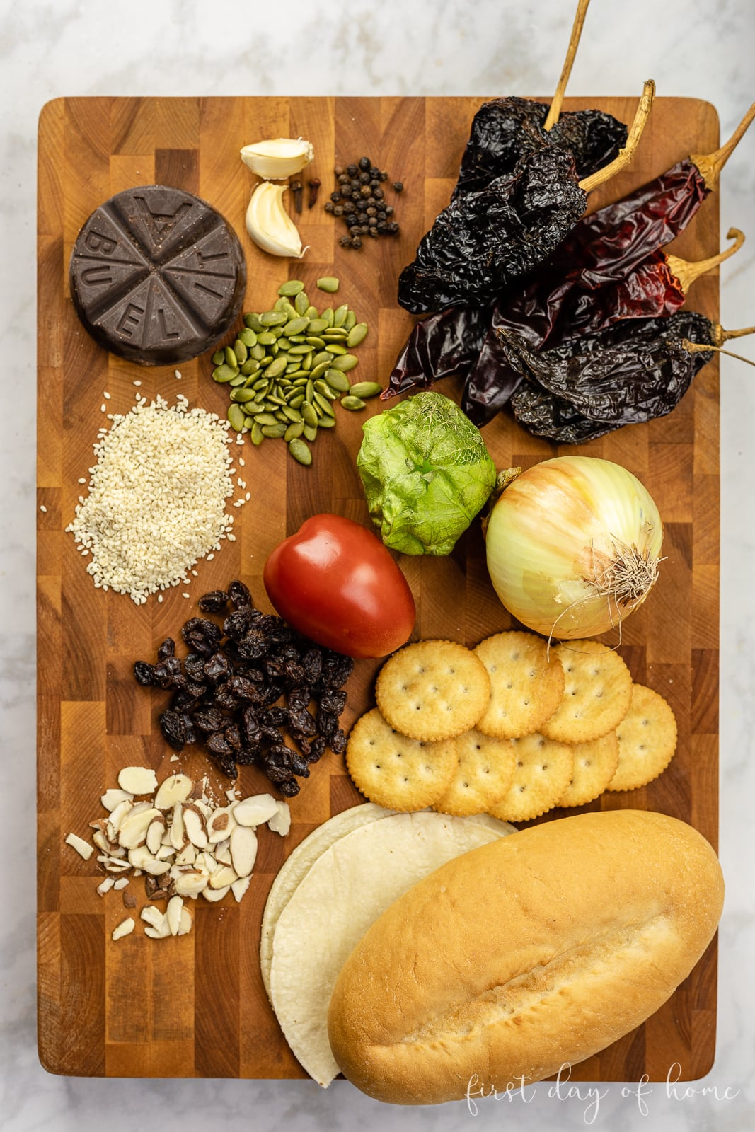 Cutting board with chicken mole sauce ingredients, including chili peppers, raisins, chocolate, onion, sesame seeds and other fruits and spices