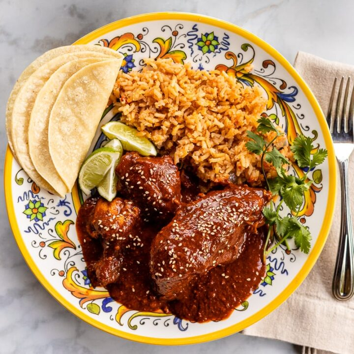 Chicken mole meal with Mexican rice, corn tortillas, and lime wedges served with a bowl of charro beans and salsa