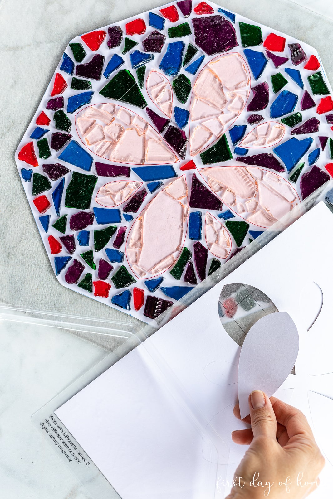 Mosaic tiles in a flower pattern and cut paper pattern