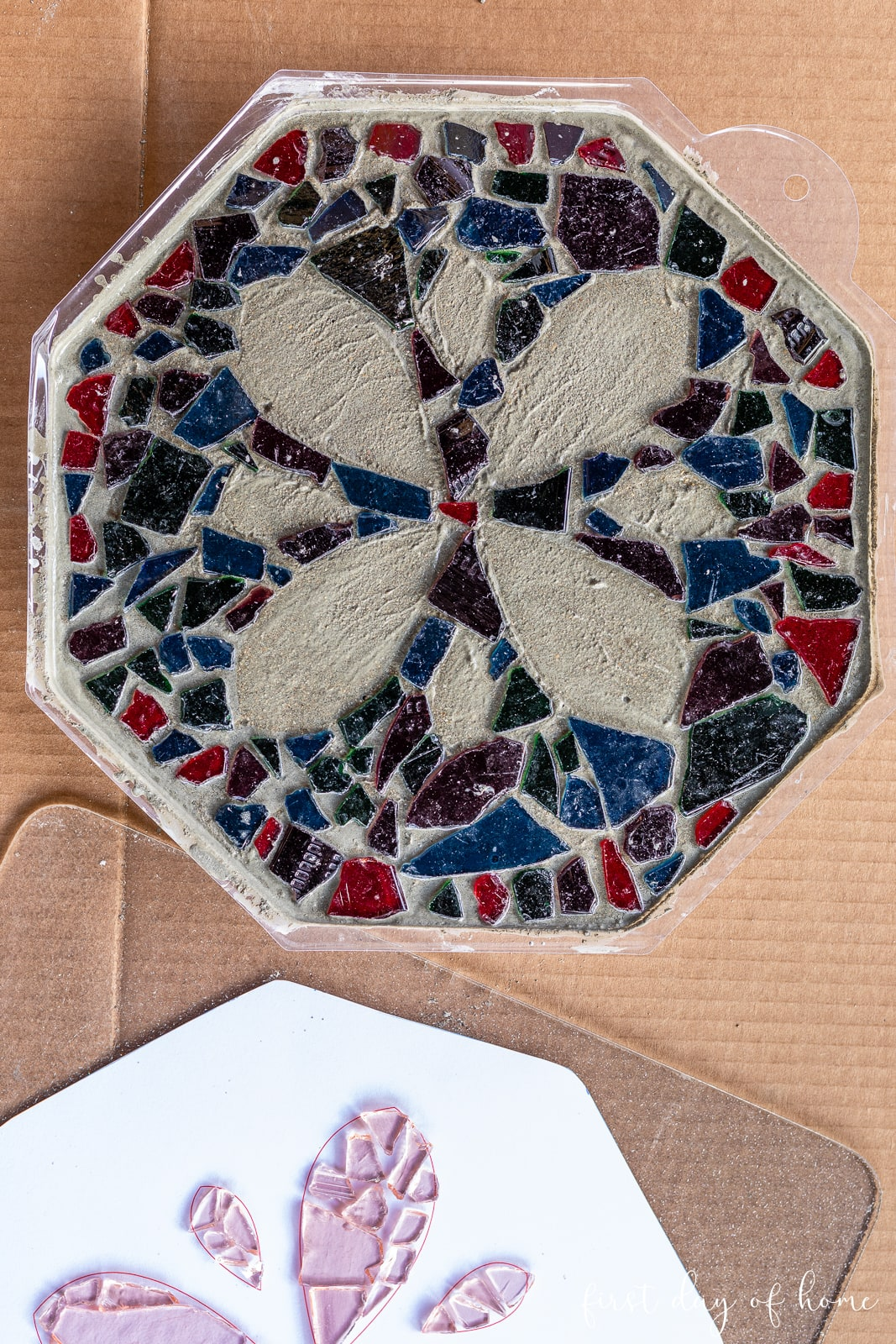 Stepping stone mix in mold with mosaic tiles being placed