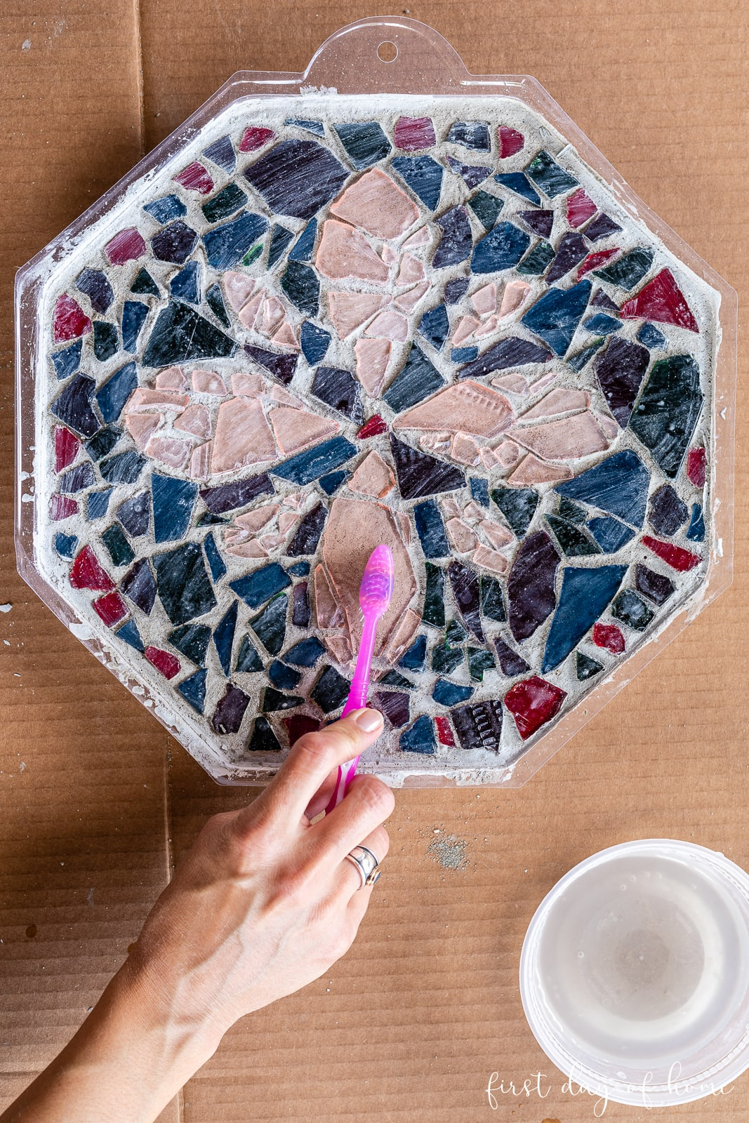 Cleaning mosaic tiles with a wet toothbrush after the stepping stone mix has dried 24 hours.