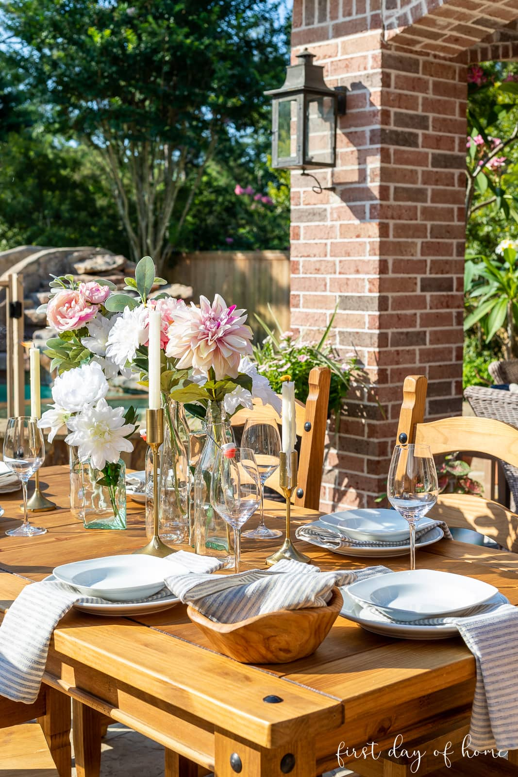 Outdoor dining table with floral centerpiece and taper candles