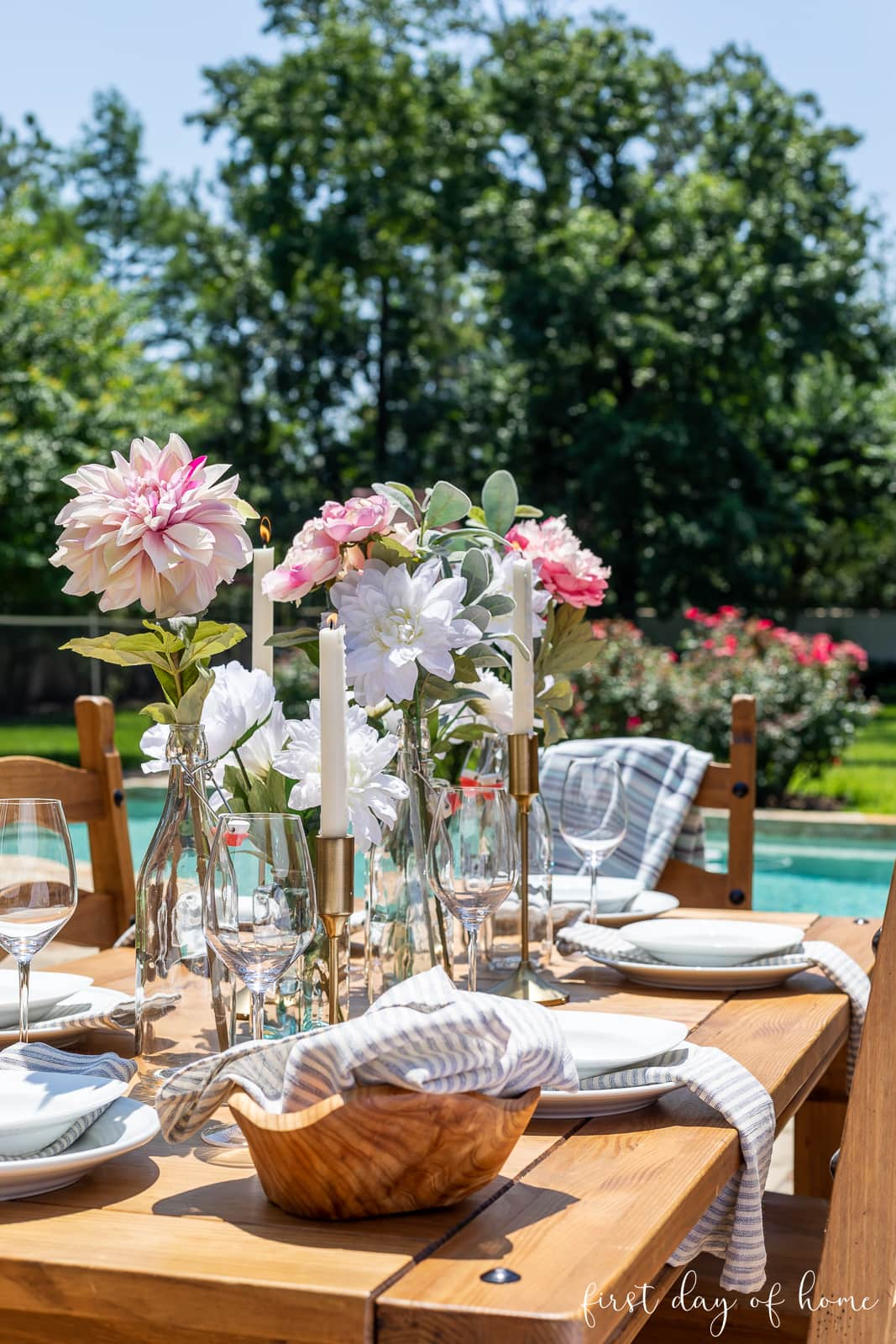 Outdoor dining table decorations with faux floral centerpiece, glass bottles and table linens