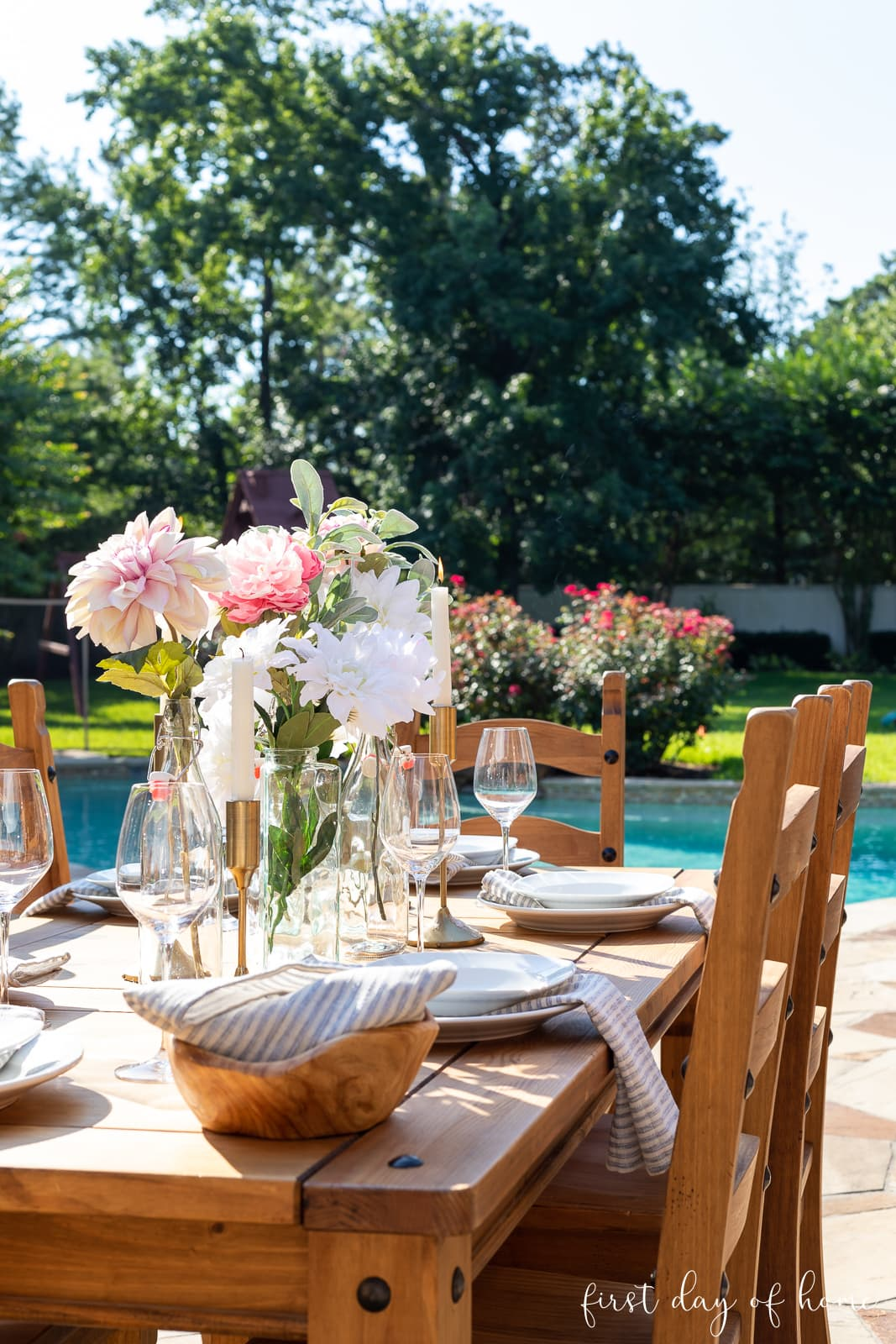 Outdoor dining table with floral centerpiece using glass bottles and taper candles