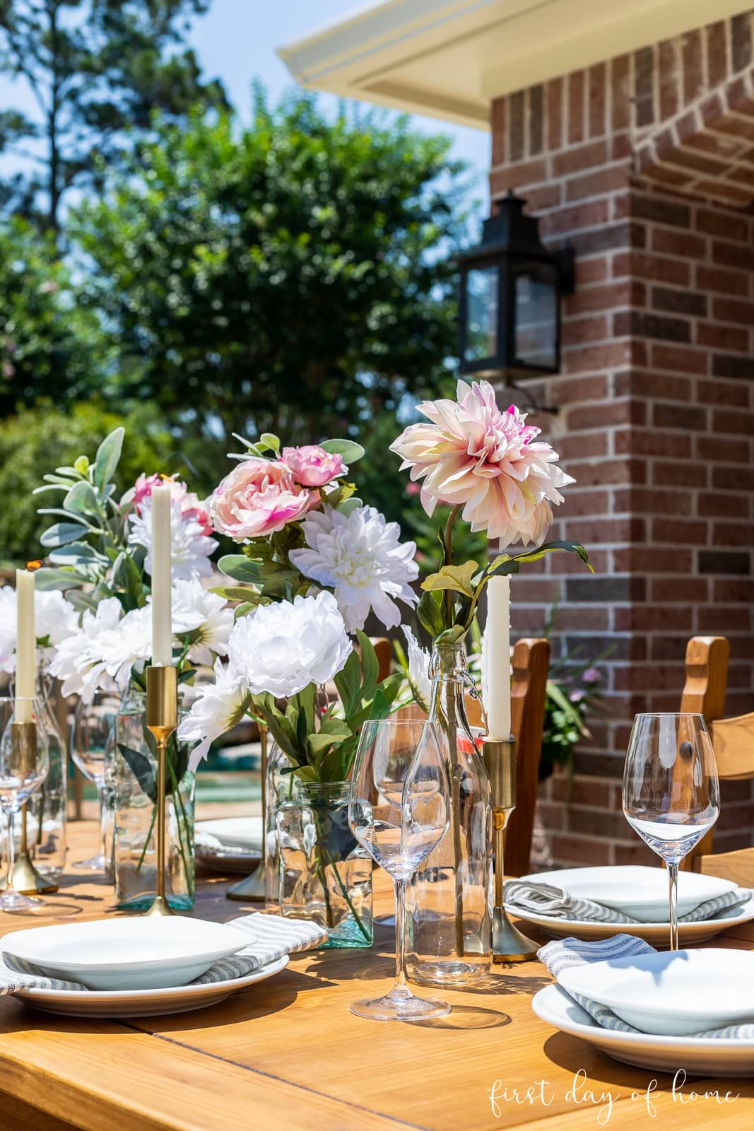 Outdoor dining table centerpiece with glass bottles and vases filled with faux floral stems